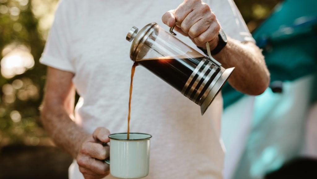 Mann schüttet sich Kaffee in Emailletasse aus French Press