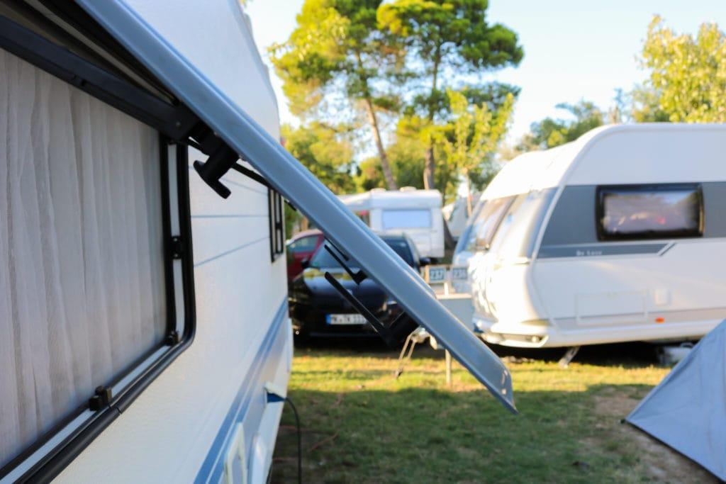 Offenes Fenster eines Campers auf einem Campingplatz