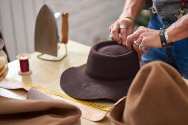 Mann produziert einen braunen Hut