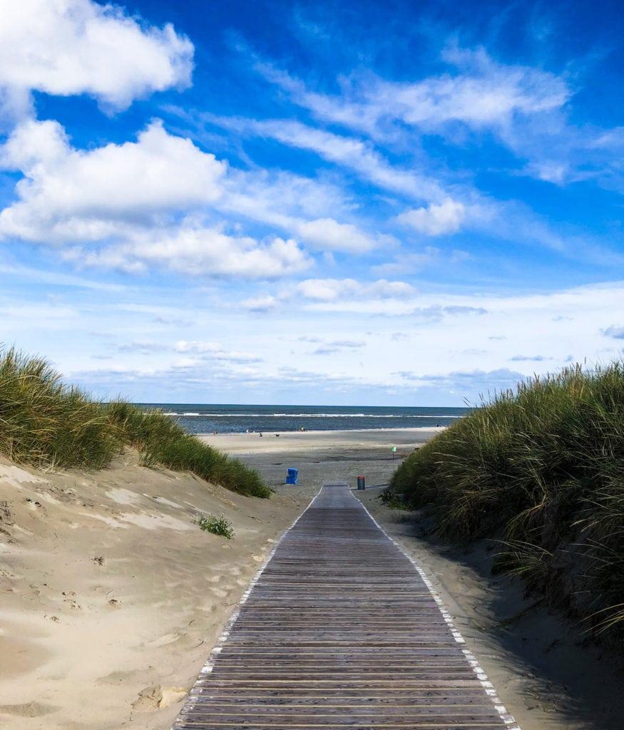 Holzsteg führt vorbei an Dünen zum Strand von Langeroog