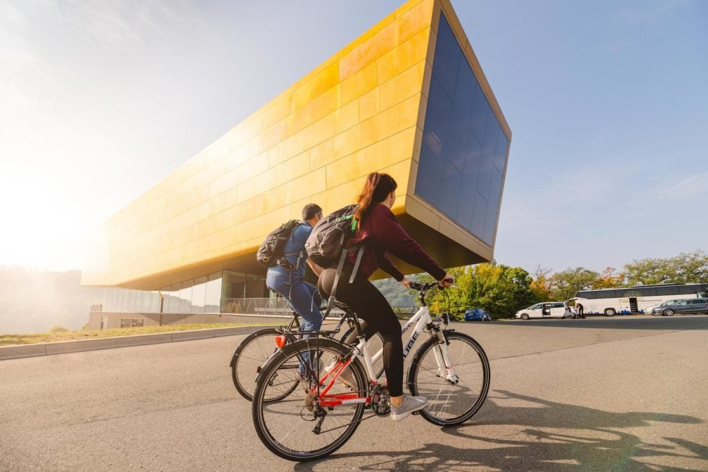 Fahrradfahrer vor der Arche Nebra, einem gelben Gebäude, das schon oft als Drehort in Saale-Unstrut gedient hat