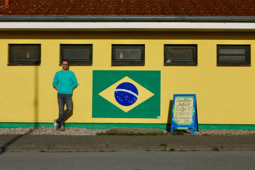 Autor Christoph Karrasch steht vor gelber Hauswand mit Brasilien-Flagge