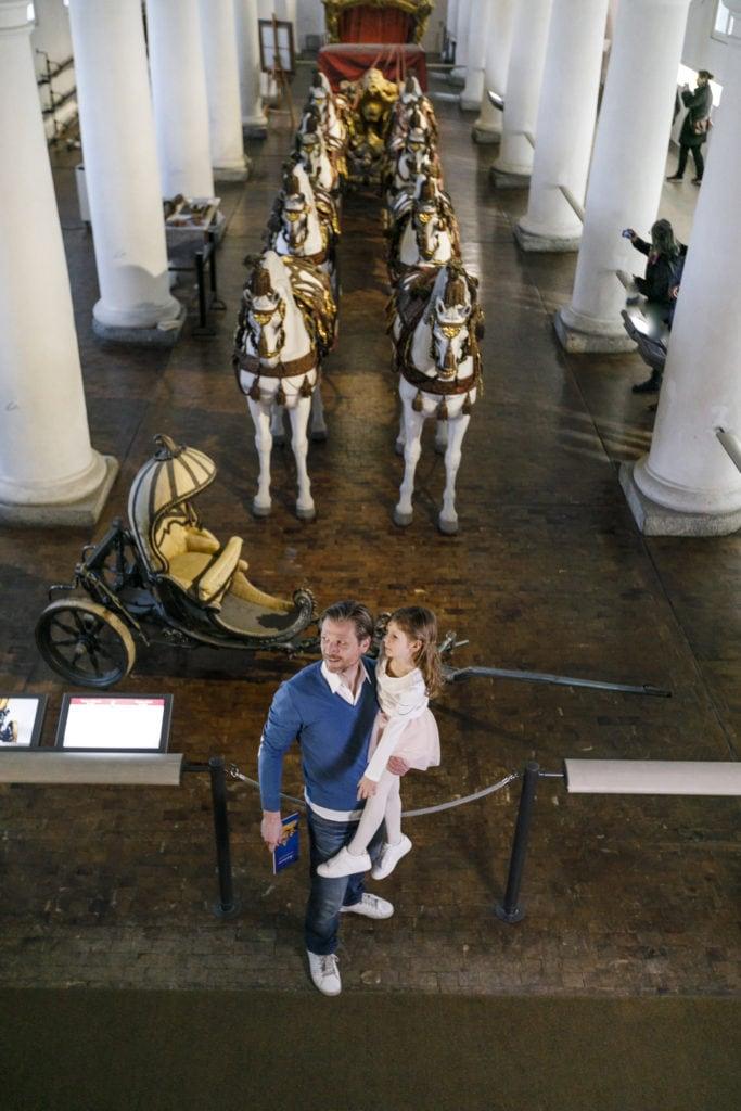 Vater steht mit seiner Tochter im Marstallmuseum in München