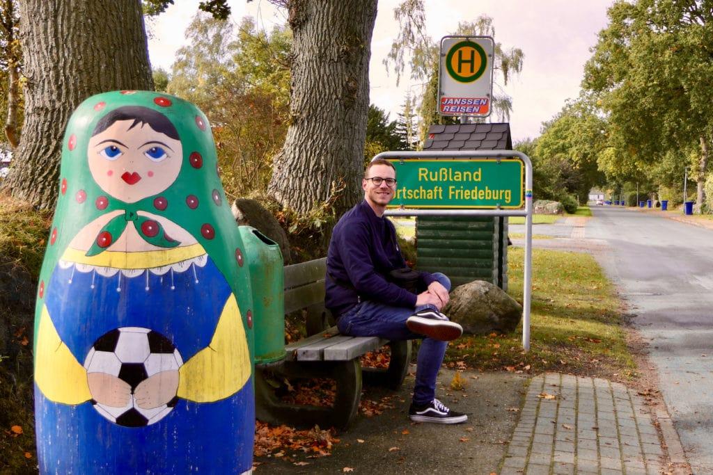 Christoph Karrasch vor dem Ortsschild in Rußland, einem Ort in Deutschland