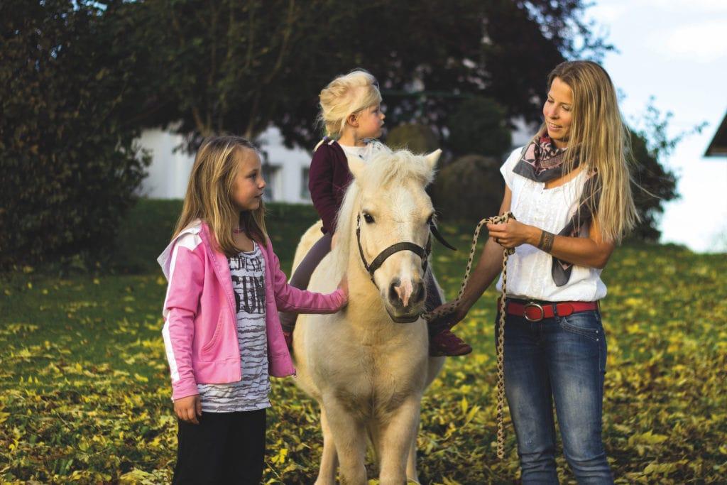 Reitlehrerin und Kinder während Reiterurlaub in Bayern