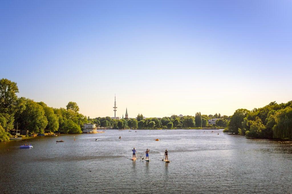 Sup-Paddler auf der Alster in Hamburg mit dem Fernsehturm im Hintergrund