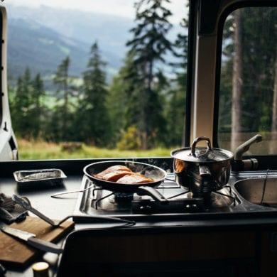 Zwei Pfannen auf einem Herd in einem Wohnmobil mit Blick auf eine Landschaft