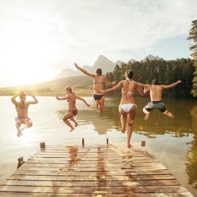Freundesgruppe springt bei gutem Wetter in den See