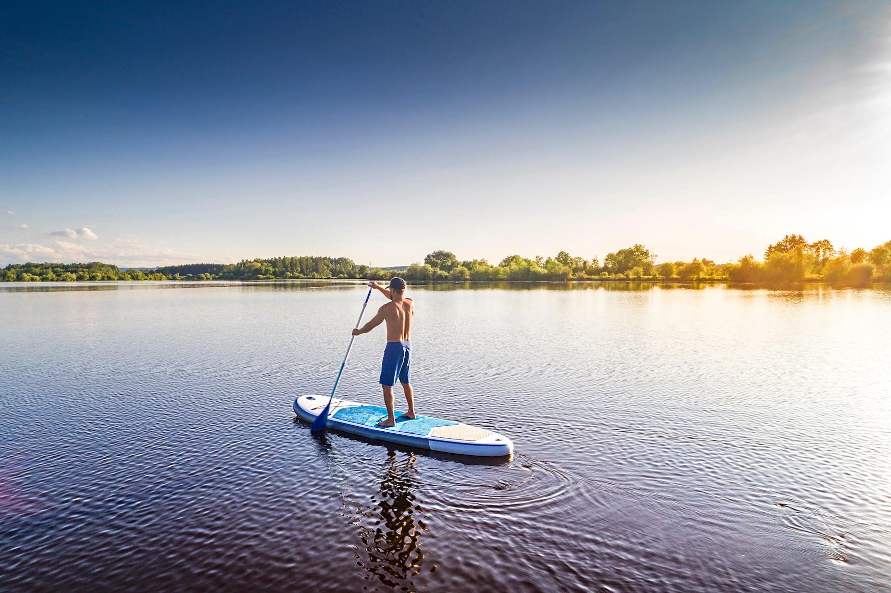 Stand Up Paddler auf einem See in Deutschland im Sommer