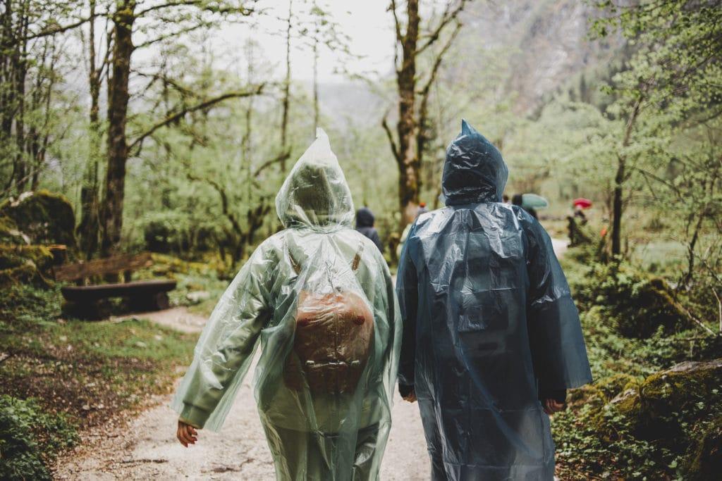 Wanderer spazieren in Regencapes durch Wald bei Regen