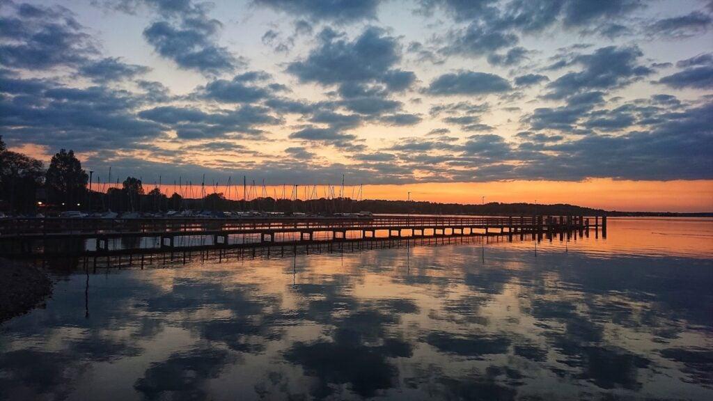 Bootssteg vor der Kulisse eines Sonnenuntergangs am Chiemsee