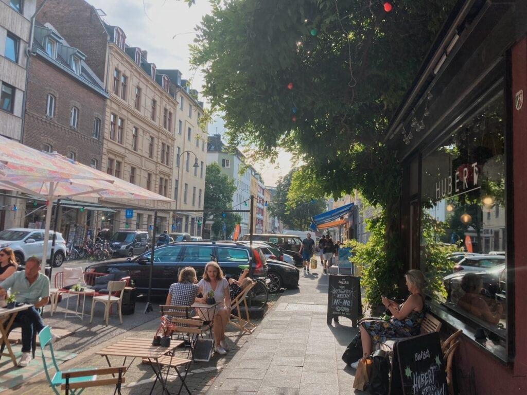 Menschen sitzen in Café Hubert auf der Merowingerstraße in Köln