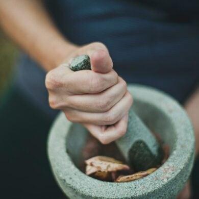 Frau mörsert Kräuter in Wald